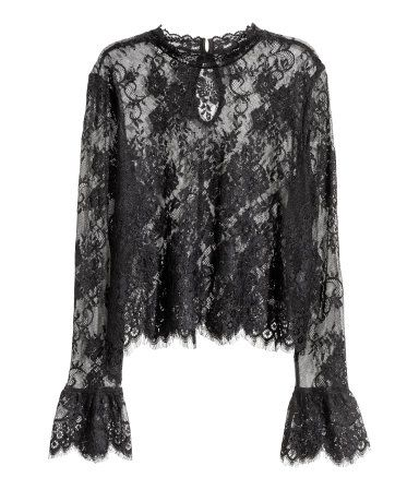 Black. Short lace blouse with a small stand-up collar, opening at back of neck with button, and long sleeves with a flounce at cuffs.