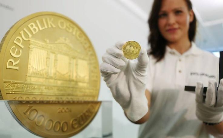 """Mulher compara a maior moeda de ouro européia durante a exposição na casa de comércio Pro Aurum em Hamburg, Alemanha; com valor de 1,3 milhões de euros e pesando 31 kg ficou conhecida como """"Big Phil"""". (Jornal FSP)."""