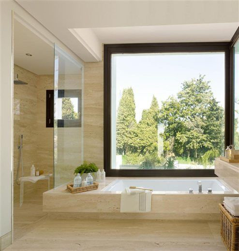 A marble bathroom open to the landscape