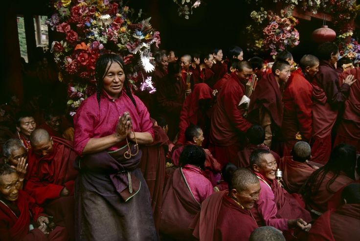 Steve McCurry   TIBET. Kham. 2000. Pilgrim praying with monks at the Buddhist academy of Larung Gar.