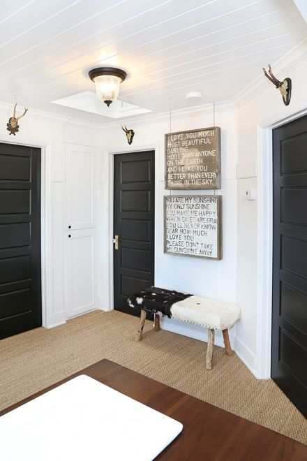 entry way color pattern. white walls with three black doors.