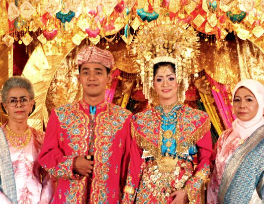 Indonesian Wedding, The stage, lit and lavishly decorated the color of gold, is shaped in the style of a traditional Padang House and is called Rumah Gadang,