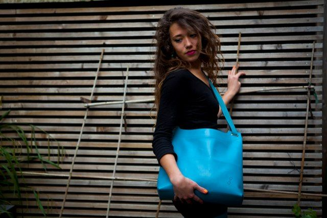 Turquoise Maxi Pop Up bag worn with over-the-shoulder strap length.
