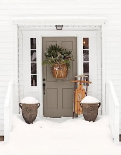 Muted front door paired with a white home.