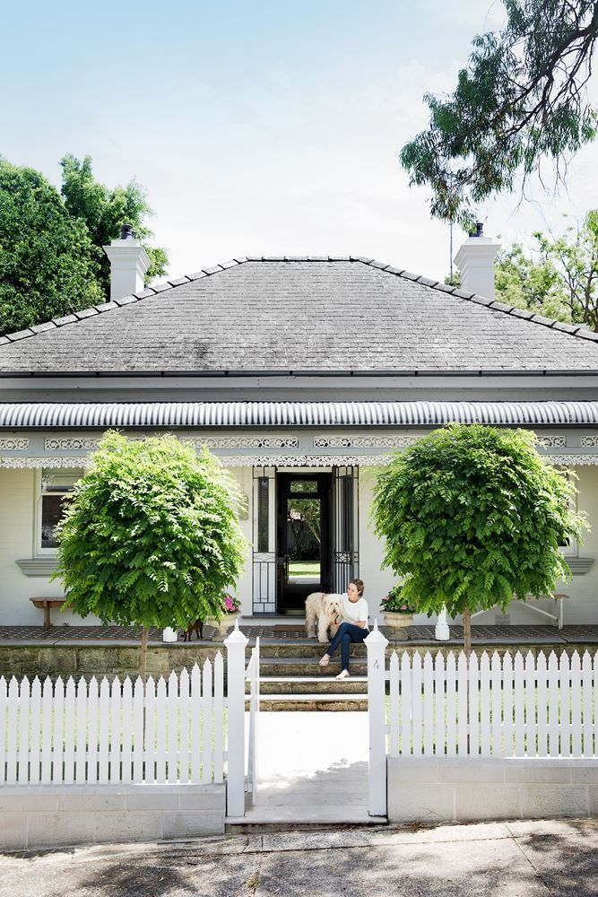 """Twin mop top robinias (*Robinia pseudoacacia 'Umbraculifera'*) uphold the strict symmetry of the classic 19th-century façade. Interior designer and homeowner [Fiona Shakespeare](http://shakespeare-design.com.au/?utm_campaign=supplier/ target=""""_blank"""") sits on the front steps with Teddy the groodle."""