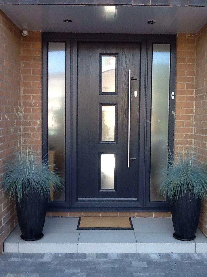 Contemporary grey front door grey with opaque sidelight window panels.