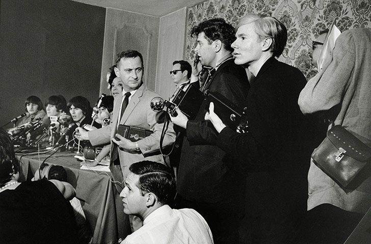 Andy Warhol, right, waits among the photographers at a Beatles press conference in New York, October, 1964 Photograph: Tony Ray Jones/Getty Images/SSPL