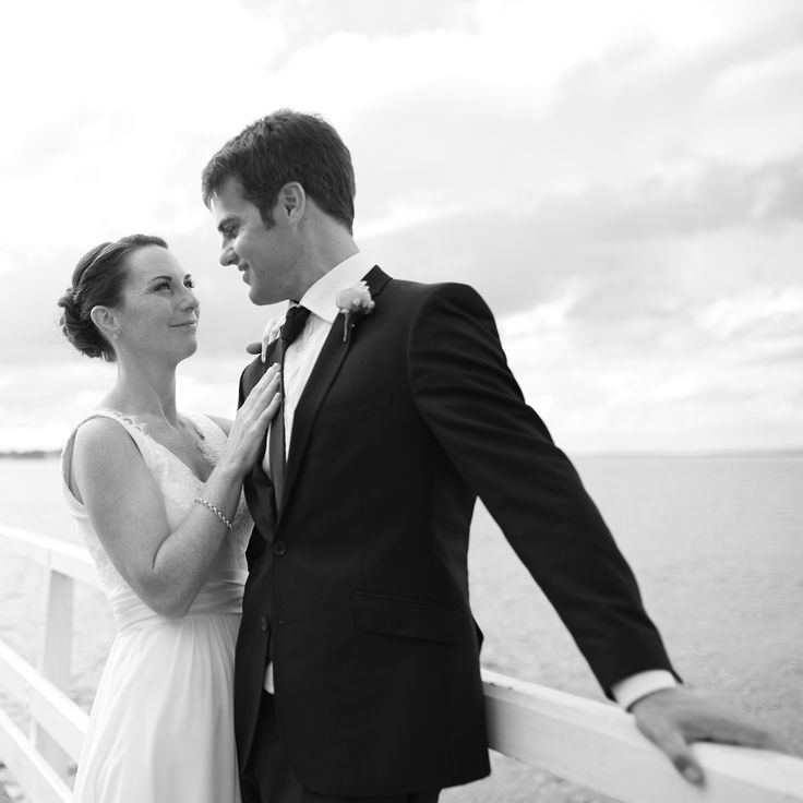 Black and white shot of a bride and groom on a jetty. Mission Bay, Auckland City, New Zealand. Captured by Adam Popovic Photography. Auckland wedding photographer.