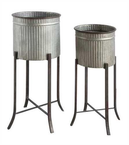 "These corrugated metal planters are a great modern farmhouse accessory! This set includes two planters and two stands in two sizes. The larger one measures 13"""" in diameter and is 12"""" high. Its overa"
