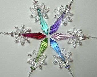 """This beautiful shining rainbow angel was created entirely with Swarovski crystals.  HOPE was created using a 40mm Strass logo-etched drop crystal and 6 Swarovski Strass lilly octagons, one each of red, orange, yellow, green, blue and purple. She is suspended from 3 inches of Swarovski crystal beads. The length from the bottom of the angel to the top bead of the strand is 5"""". The length, including the 1"""" loop hanger, is approximately 6½"""". The width of the wings is 1¼"""". This is the ideal…"""