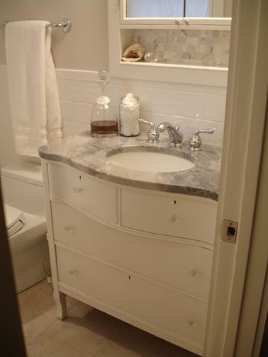"""We used an old oak bureau we got for $40, painted it, modified the drawers to fit around the plumbing, added modern drawer glides for functionality, vintage crystal knobs from eBay, and a top made from a """"remnant"""" piece of Vermont White quartzite. Low budget, big impact :)"""