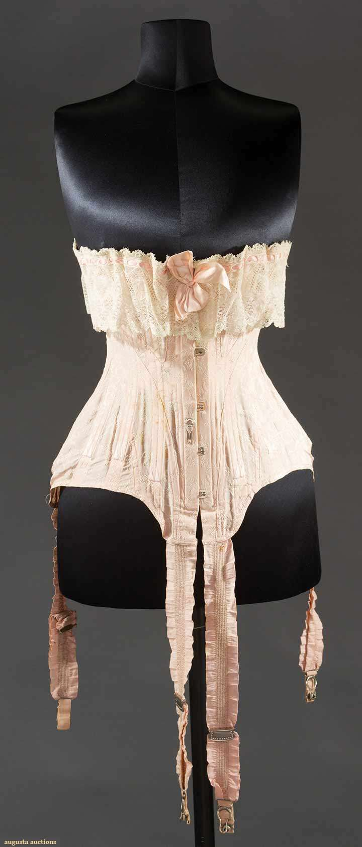"Pink brocade ""kabo"" corset, America, c1905. Cotton blend in small blossom and bow brocade, Four attached garters, lace top flounce, Waist 23"" and up, Length 13"""