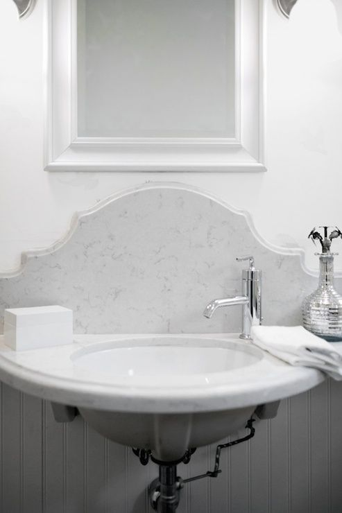 Chic bathroom boasts upper walls clad in light gray dove wallpaper and lower walls clad in white beadboard trim framing white beveled mirror over wall-mounted white marble sink framing oval sink and off-set deck faucet paired with curved marble backsplash.