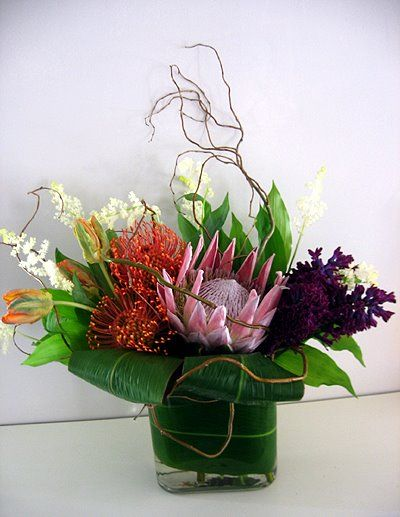 Tropical arrangement with king protea, pin cusion protea, stock & green leaves