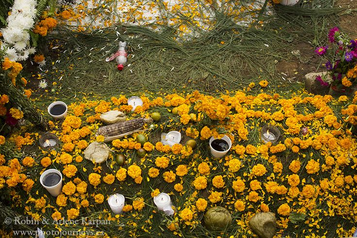 Offerings left by a grave that is covered with yellow marigold petals in the cemetery of Sumpongo, Guatemala, All Saints Day - Photo Journeys