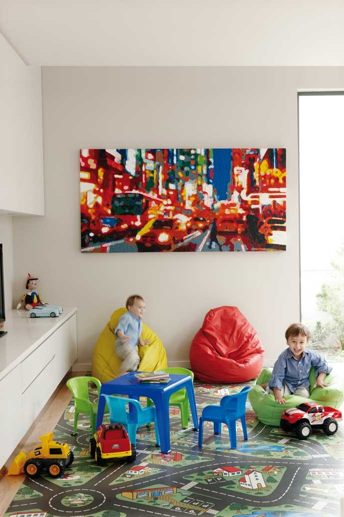 This boys' playroom is a fun space, with beanbags, toys and colourful matting. The handle-free cabinetry turns one wall into storage.