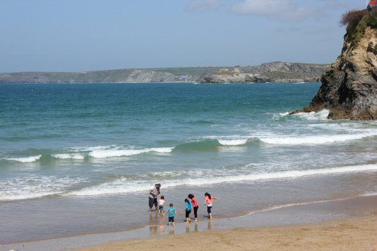 Kids splashing in the waves on Towan Beach in Newquay, Cornwall, perfect for a family holiday with the Blue Reef Aquarium nearby.