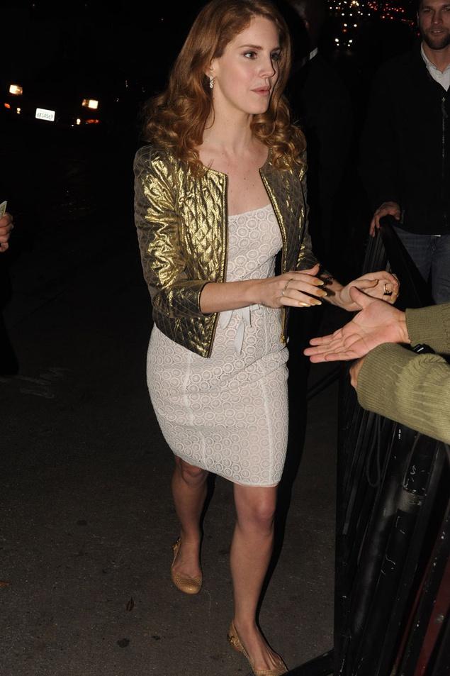 Lana del Rey con vestido de encaje y chaqueta dorada acolchada... los flats me hacen ruido pero me gusta su stylo!