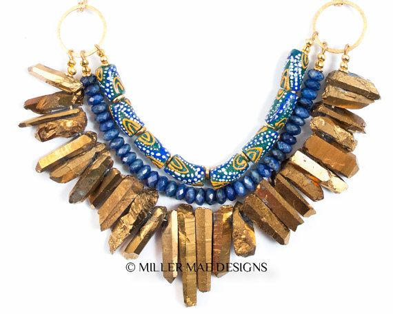 Statement Collar featuring Gold Quartz Spikes, Sodalite gemstones, and hand-painted African Tribal Beads.  * Necklace Length: 17 adjustable to 19 inches * Spikes avg. 20-40mm long * Lobster Claw Clasp  NOTE: This is the exact necklace you will receive!! This is not a stock photo!  These stunning krobo beads are handmade in Ghana from the Asante and Krobo Tribes in an initiative for the empowerment of Ghanian women. This tribal spike necklace is the ultimate statement necklace, and pairs…
