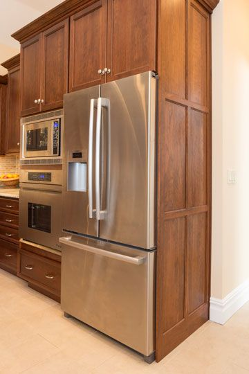 the refrigerator is housed in a cabinet with decorative panels on