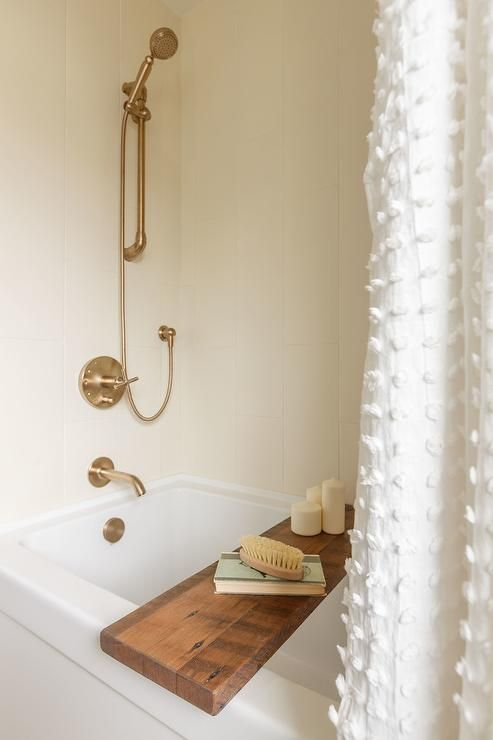 A White Tassel Shower Curtain Hangs In Front Of Drop Bathtub Accented With Wood Tray And Brushed Gold Kit Fixed To Surround Tiles