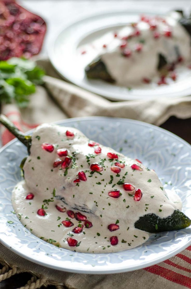 Vegan Chiles en Nogada, roasted poblano chile is stuffed with an aromatic picadillo, covered in walnut cream sauce and pomegranate seeds. #veganmexican