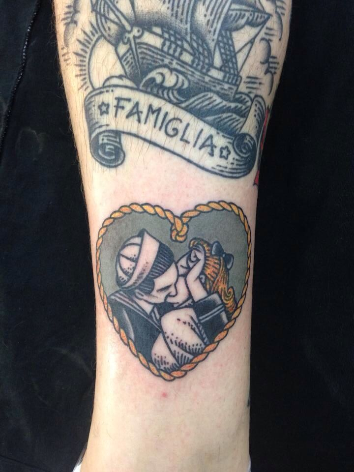 Traditional sailor heart tattoo of a young vintage couple kissing