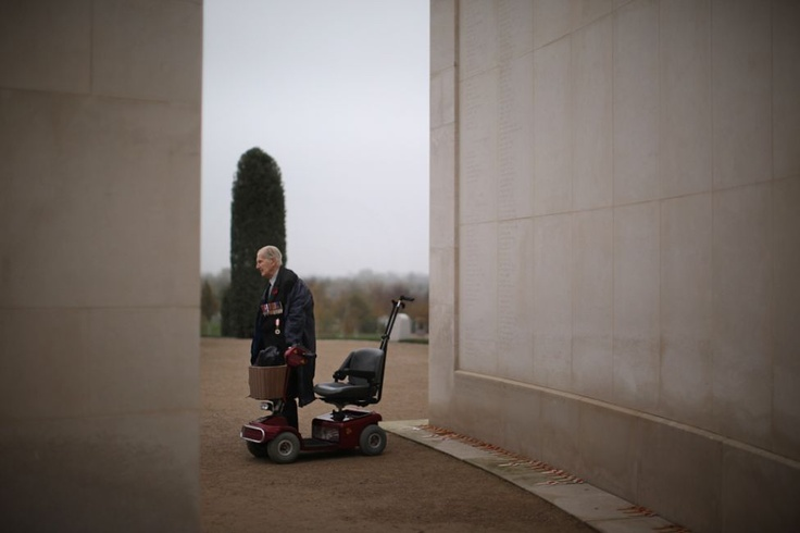 Veteran Philip Malins, Age 92, stands next to his mobility scooter as he takes part in a two minute silence at the Memorial Arboretum on Armstice Day in Alrewas, UK, Nov. 11, 2011 (Chritopher Furlong - AFP/Getty Images)