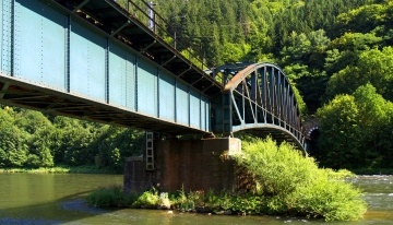 Summer view railroad bridge and tunnel above the Vah river near Strecno, in Slovakia.