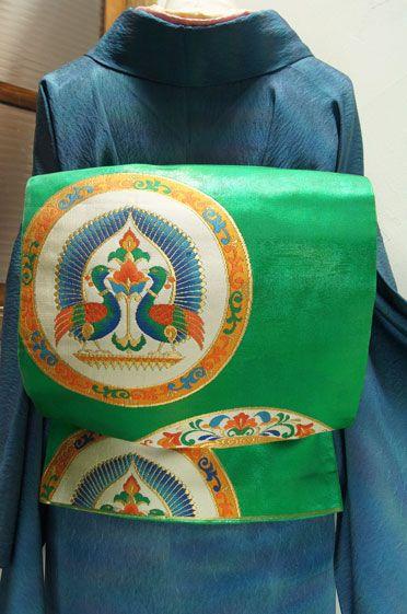 マラカイトのような深く美しい緑に、向かい合う孔雀や、ヨーロッパのビンテージファブリックを思わせるような大きな丸模様が織り出された袋帯です。