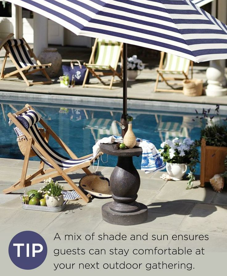 A poolside patio with a striped umbrella