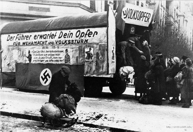 """С увеличением количества ополченцев из Фольксштурма, германское командование стало испытывать нехватку снаряжения и одежды. Чтобы восполнить дефицит, власти организовали Фольксопфер – кампанию по сбору одежды и обуви, которую гражданские должны были пожертвовать для ополченцев. Надпись: """"Фюрер надеется на ваши пожертвования для армии и ополчения. Если вы хотите, чтобы ополченец ходил в форме, опустошите свой шкаф и несите одежду сюда"""". 12 февраля 1945 года. (AP Photo)"""