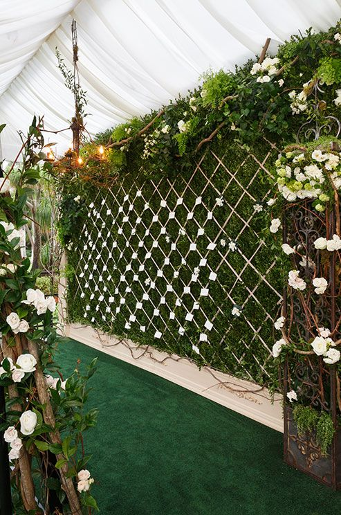 Forego a traditional escort card table for a quilted garden wall overgrown with lush greens, vines and white roses.