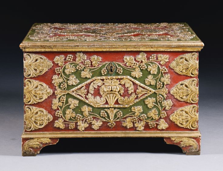 A LARGE OTTOMAN EDIRNEKARI BRIDAL CHEST, TURKEY, 19TH CENTURY of rectangular form, painted with red and green backgrounds, the decoration carved in relief and gilded, designed with bouquets of fruit framed by scrolling grapevines and foliate motifs, the hinged cover opens to reveal a small internal compartment 95 by 59 by 53.5cm.