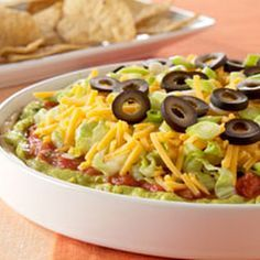Philadelphia 7-Layer Mexican Dip Recipe Appetizers with Philadelphia Cream Cheese, Taco Bell Taco Seasoning Mix, guacamole, TACO BELL® Thick & Chunky Mild Salsa, shredded lettuce, KRAFT Shredded Cheddar Cheese, green onions, sliced black olives
