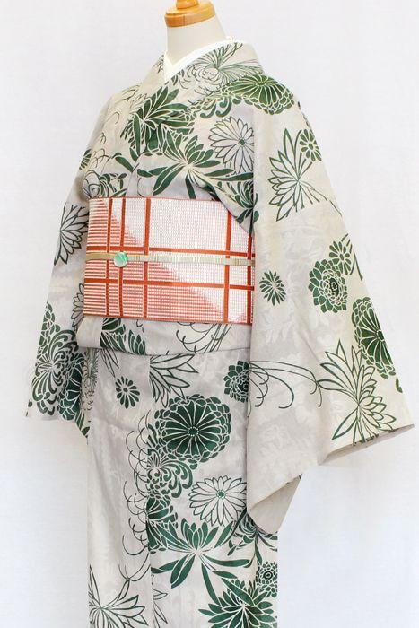 《今日の着物コーディネート》ひでや工房のからみ織の綿着物に、格子柄の半幅帯を合わせた和風美人なコーディネートです。様々な形の菊を緑一色だけで染めた粋なデザイン。菊の花には濃淡のついた色挿しが施されており、着姿に深みのある雰囲気を添えます。