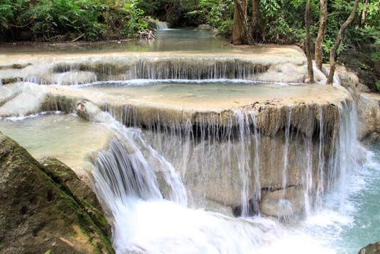The Magical Waterfalls Of Erawan National Park, Thailand. This one is dubbed as the spa waterfall. The tiered pools are shallow and this allows the fish to congregate & nibble on your feet kinda like having one of those fish pedicures.