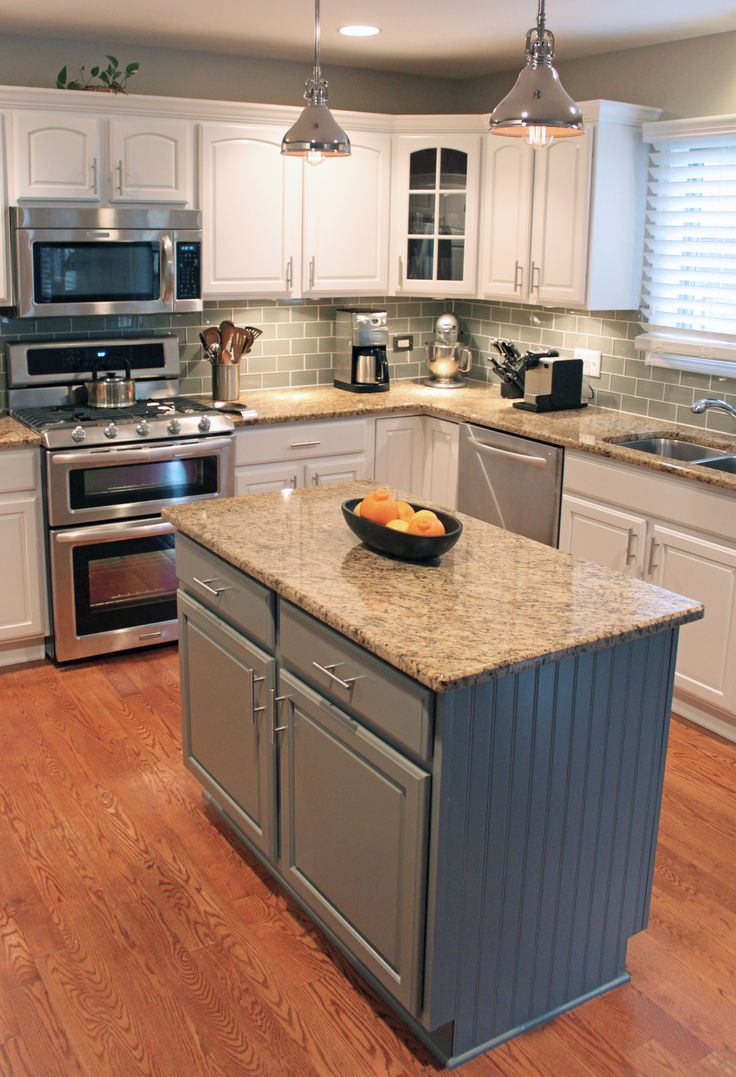 Kitchen remodel with painted cabinets and island, new backsplash, new stainless steel appliances and lighting.