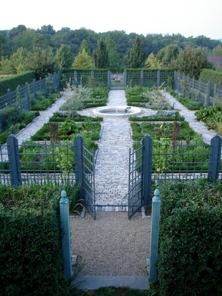"""A double """"walled"""" (hedge and fence) Potager (Kitchen) Garden with a circular pool as the center feature."""