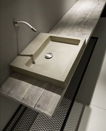 Line of suspended wash basins in cement (material): grey, white or red coloured in the mass. Trendly forms made out of unusual materials performing highly functional essentiality that becomes formal synthesis. Dedicated to those who search for non conventional decorative elements that can reproduce stylistic and aesthetical innovation.