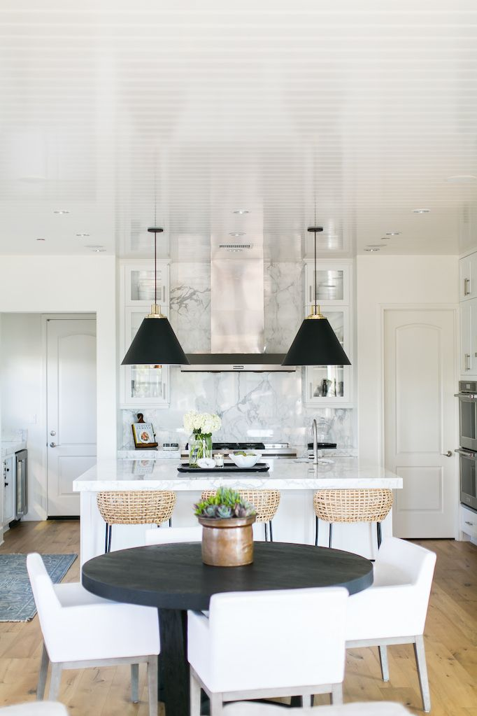 BECKI OWENS- Estillo Project: Classic Modern Kitchen. A white kitchen  with statuary marble, Benjamin Moore Swiss Coffee paint, black cone pendants, rattan counter stools, round black dining table with linen dining chairs.