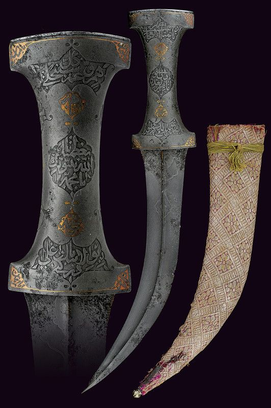 """Kard from Private Collection of Oriental Weapons. Origin: Turkey  Dating: 18th Century    Description: Curved blade with two wires in damask, ribbed with carvings in the center and at the base, areas with rust damage; handle damask double """"T"""" containing seven cartouches with inscriptions in Arabic and bronze inlay. Wooden scabbard covered with brocade and silver ferrule.    Dimensions: length 34 cm."""