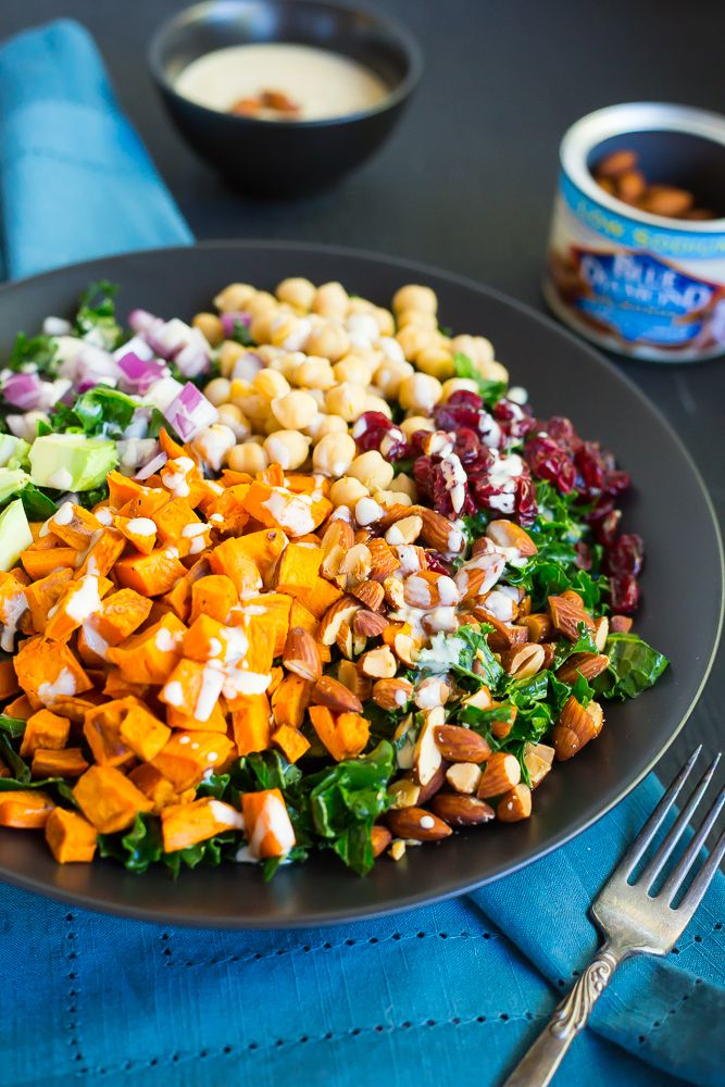 VEGAN This Chopped Kale Power Salad with Lemon Tahini Dressing is the perfect salad to start the New Year with!  Eat it for lunch and you'll have energy all day!  Packed with healthy and delicious ingredients, including: sweet potato, chickpeas, almonds, avocado, cranberries and red onion!