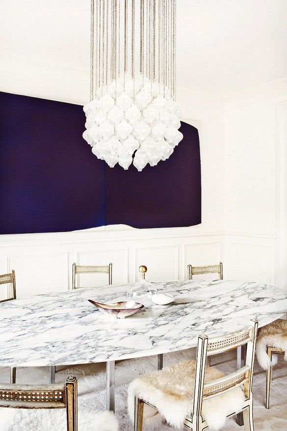 Luxe, modern dining space with marble dining table, sheepskin-covered chairs, and intricate crystal chandelier.