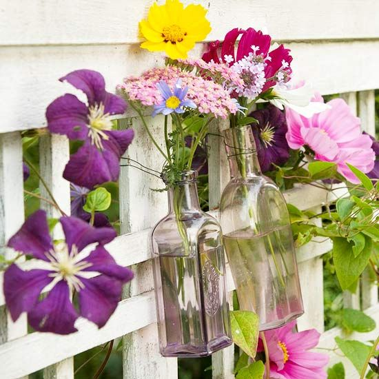Perfect for a garden trellis or front door, a small bouquet of spring flowers tucked into clear glass bottles makes a natural statement. Fill recycled glass bottles with your favorite flowers, mixing up the colors for a pretty spring decoration. To make this arrangement work on your front door, wrap wire around the bottle necks to secure to a door knocker or nail.