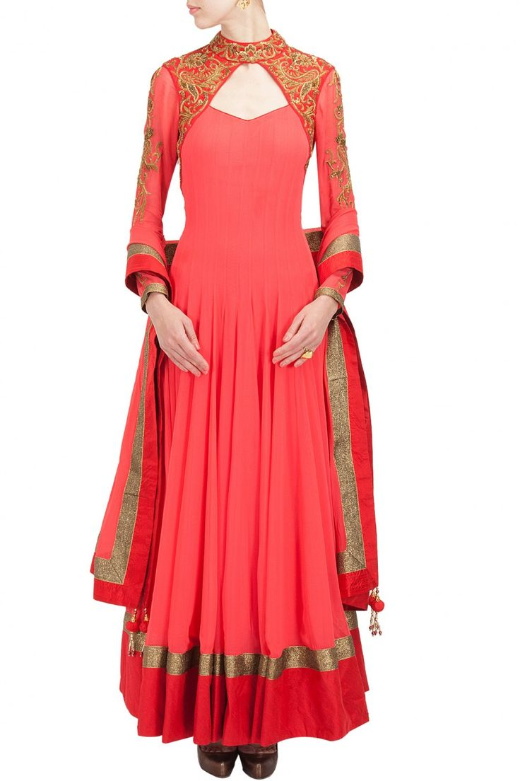 This anarkali suit is featuring in coral color with floral pattern zardosi embroidered top collar, shoulder panels and sleeves. This anarkali suit has a cut out back and comes along with matching chur
