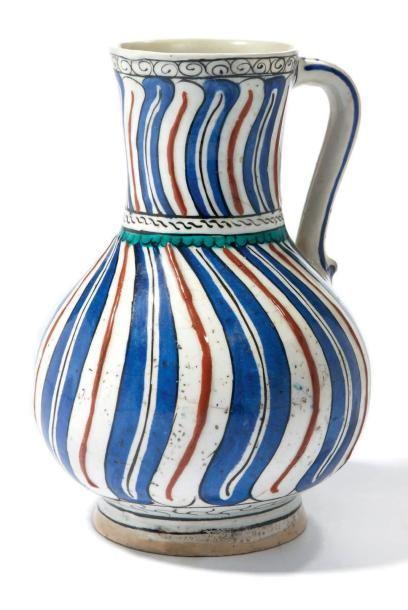 PICHET D'IZNIK VERS 1585 en céramique siliceuse à décor tourbillonnant, décorée en rouge vif, bleu de cobalt, vert et brun sur un fond bien blanc. (petites restaurations) Turquie, Iznik, vers 1585 Haut.… - Millon & Associés - 01/06/2015