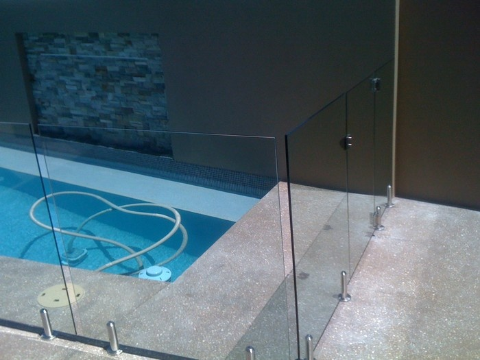 Frameless pool fencing and polished concrete floors no coping tiles