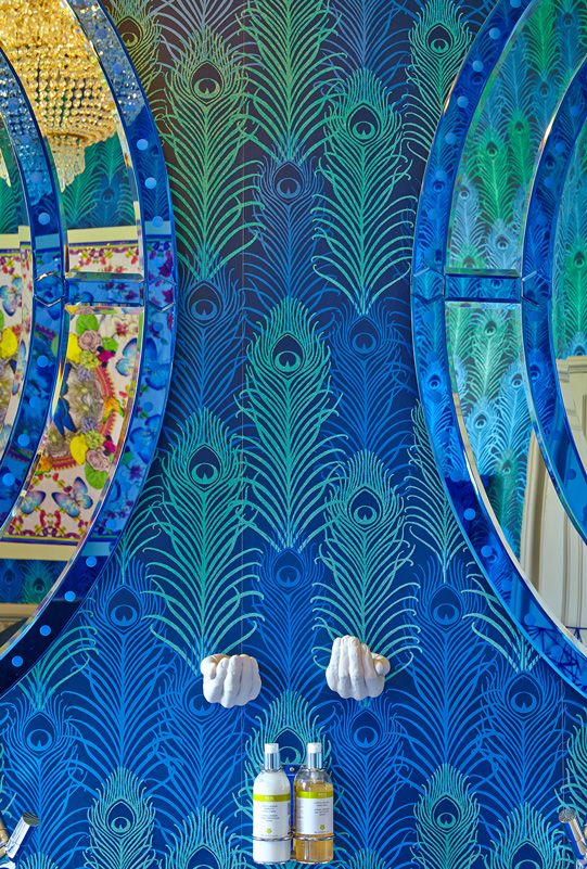 Blue and green peacock wallpaper from the Osborne and Little Eden collection cover the bathroom in the Matthew Williamson suite at Aynhoe Park. The interior of the bathroom features two oval mirrors, cupped hands that serve as soap holders and two bottles of lotion. There is a reflection of the rainbow framed silk butterfly scarf hanging on the wall in the mirror.