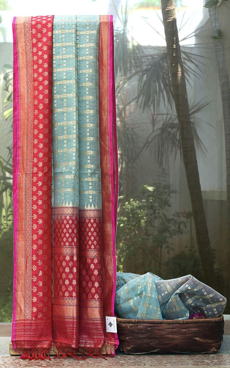 This striking sky blue sari is a light benares kora has broken checks all over in gold zari and fawn tan thread work. The border is in dark pink color with delicately woven lotus bhuttas in gold sa…